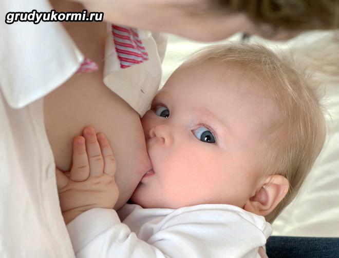 Маленький ребенок кушает грудное молоко