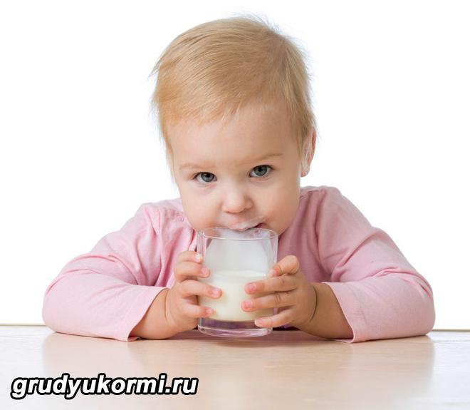 Ребенок пьет кефир за столом