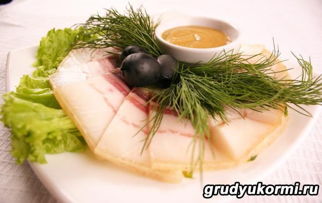 Сало с оливками, зеленью на блюдце