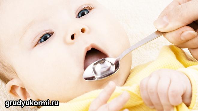 Малышу дают лекарство с ложечки