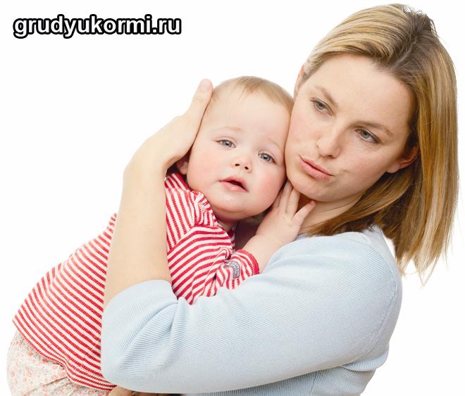 Мама держит ребеночка на руках и успокаивает его