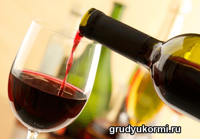 Из бутылки наливают красное вино в фужер