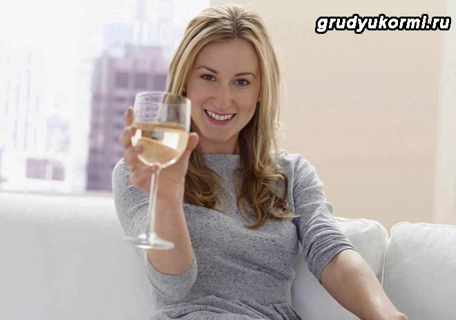 Девушка сидит на диване и держит бокал белого вина