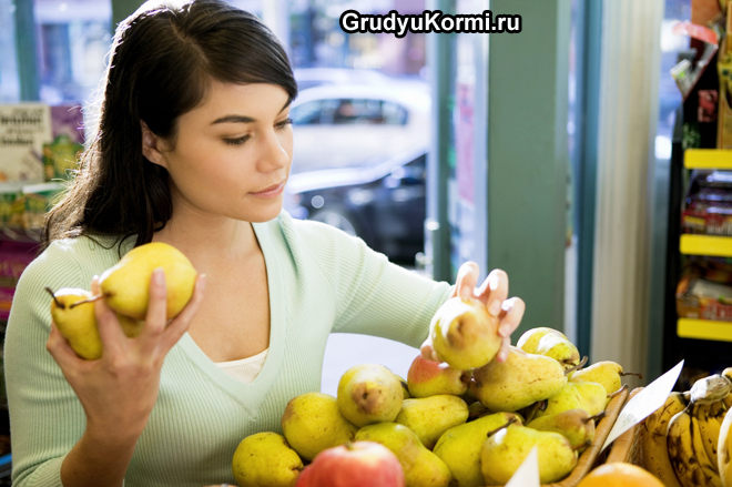Девушка выбирает груши в магазине