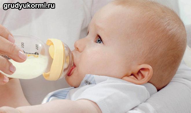 Ребенок пьет молоко из детской бутылочки