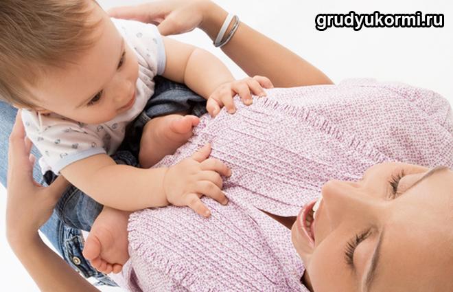 Малыш сидит на коленках у мамы