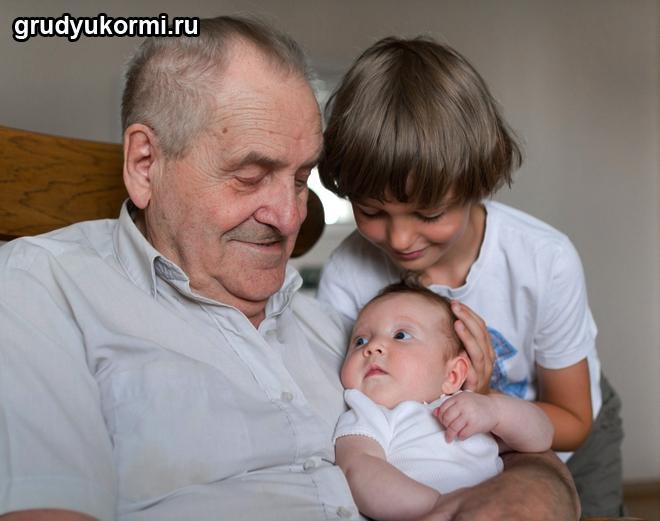 Дедушка и братик сидят с грудным ребенком