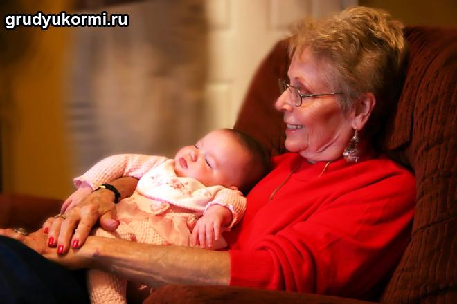 Бабушка сидит на кресле с грудным внучком