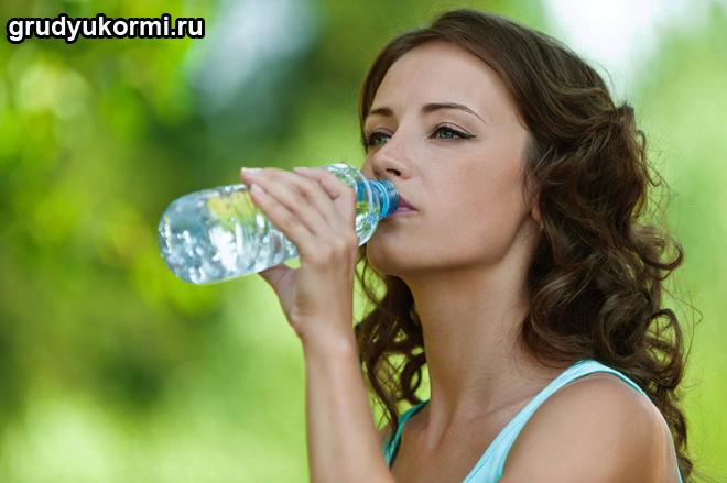 Девушка пьет воду из бутылочки