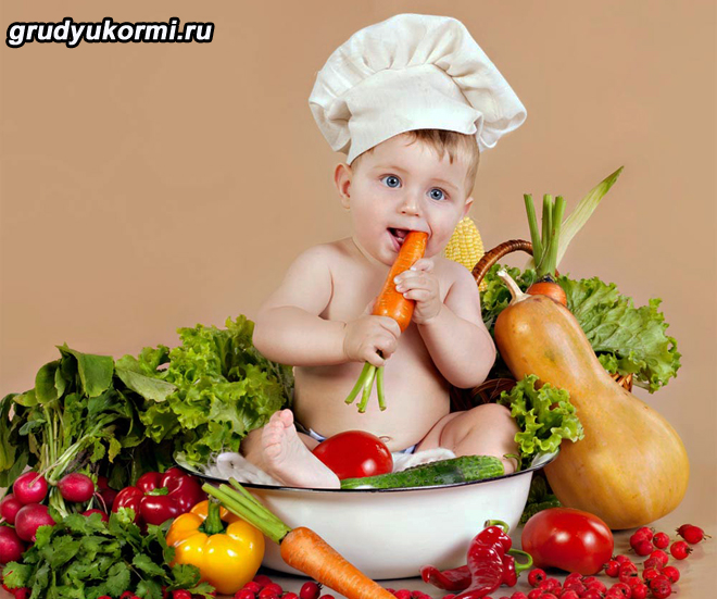 Малыш в колпаке повара и овощи