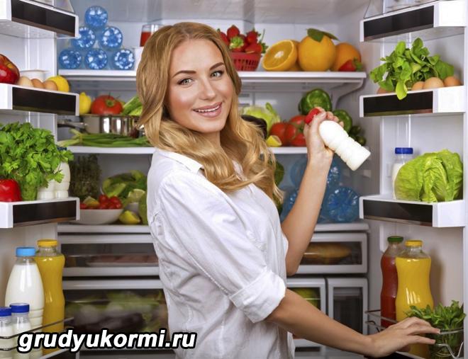 Девушка достает из холодильника бутылочку кефира