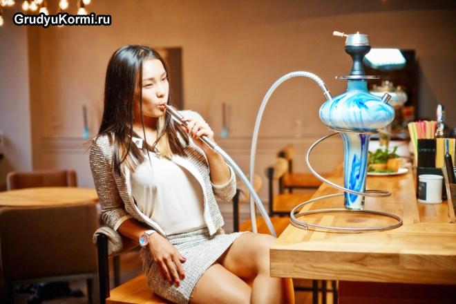 Девушка сидит за столом и курить кальян