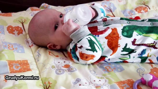 Грудной малыш пьет из бутылочки