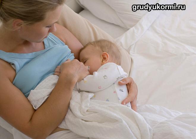 Девушка лежит в кровати под одеялом и кормит грудью ребенка