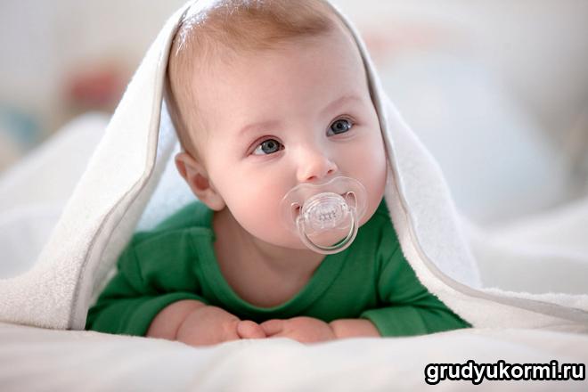 Малыш под одеялом с соской