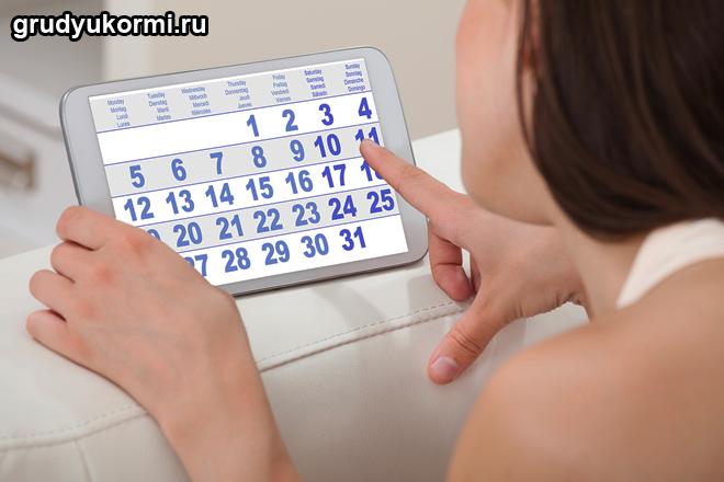 Девушка смотрит на планшете в календарь