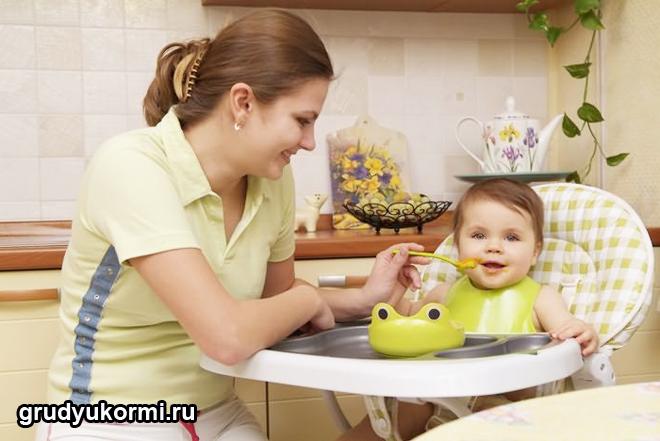 Мама кормит ребенка в детском кресле
