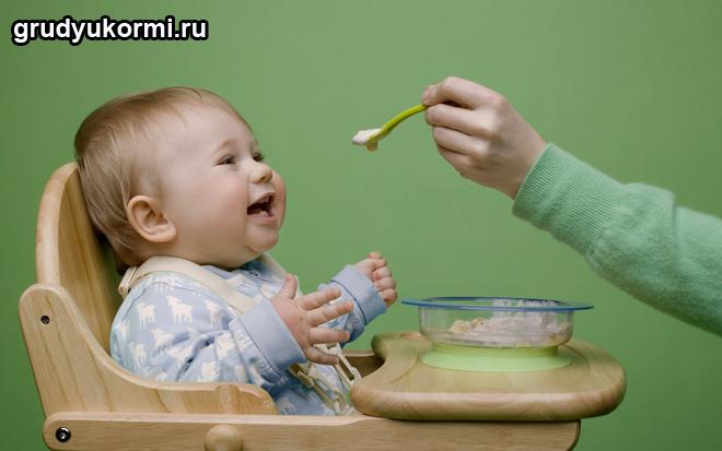 Улыбающийся малыш кушает с ложечки