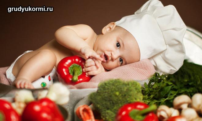 Ребенок в колпаке повара лежит в овощах