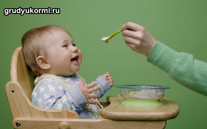 Малыша кормят с ложечки пюре