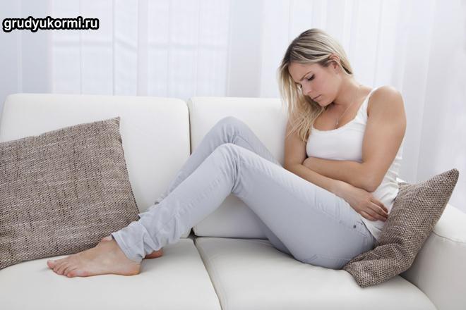 Девушка с больным животом сидит на диване